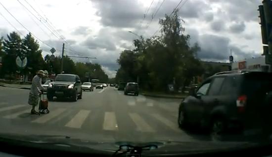 Para su coche y ayuda a una anciana a cruzar el paso de peatones