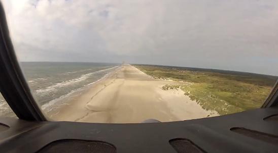 Un avión C-130 Hercules aterrizando en la playa