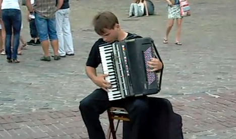 Artista callejero tocando Vivaldi con un acordeón