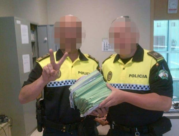 Dos policías locales de Sevilla posando con las multas impuestas durante la Feria de Abril