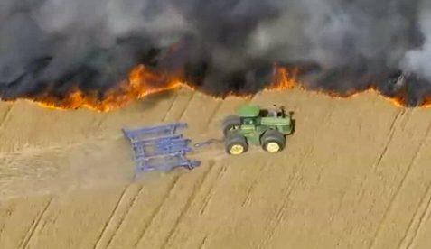 Un agricultor hace un cortafuegos con su tractor