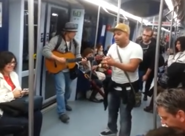 Artista callejero improvisando pasajero a pasajero en el metro de Madrid