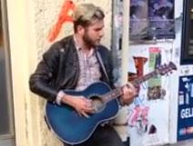 Un artista callejero tocando la guitarra en la calle... con final sorpresa