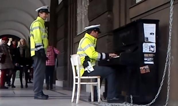 Policía tocando el piano en una calle de Praga