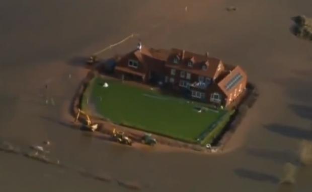 Un hombre salva su casa de las inundaciones con la excavadora