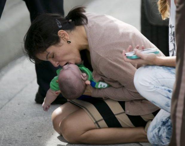 Una mujer salva con un boca a boca a un bebé en medio de una carretera