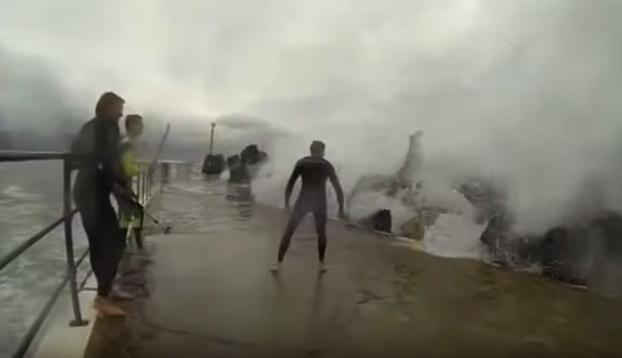 Varios amigos se colocan en un rompeolas para intentar aguantar los golpes de las olas