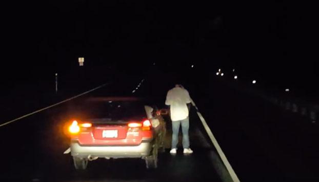 Este conductor borracho para su coche en mitad de la carretera para mear
