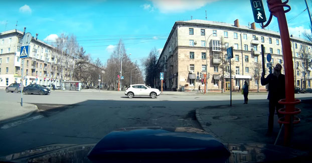 Un peatón se da cuenta que el semáforo está torcido y lo intenta arreglar