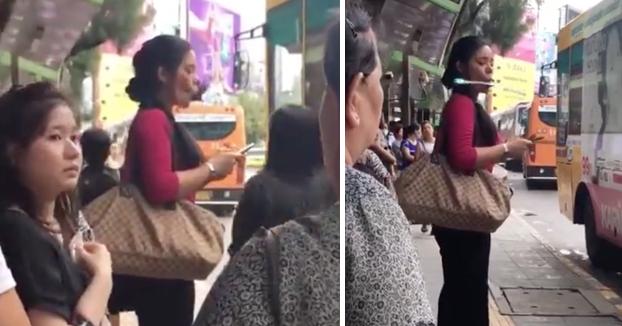 Una mujer utiliza un dispositivo de fitness facial en una parada de autobús y deja desconcertados a los allí presentes
